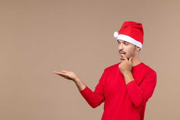 Junges männliches denken der vorderansicht auf dem feiertag der männlichen farbemotionen des braunen hintergrunds