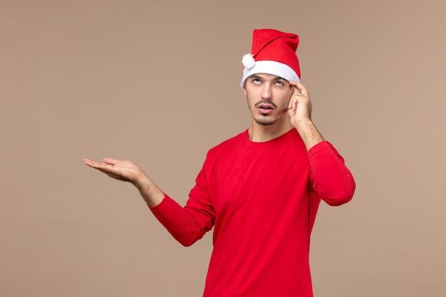 Junges männliches denken der vorderansicht auf den weihnachtsemotionen eines braunen hintergrundfeiertags