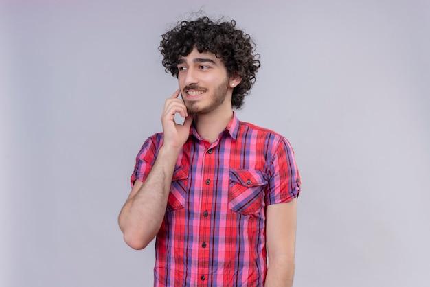 Junges männliches lockiges haar isolierte buntes hemd, das kinn kratzt