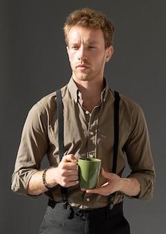 Junges männliches modell der vorderansicht, das eine tasse kaffee hält