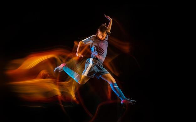 Junges männliches sportliches modelltraining in aktion, das ball tritt
