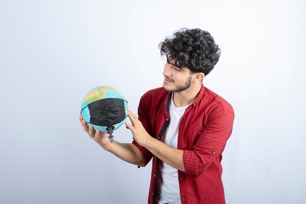 Junges mannmodell, das eine erdkugel mit medizinischer maske hält.