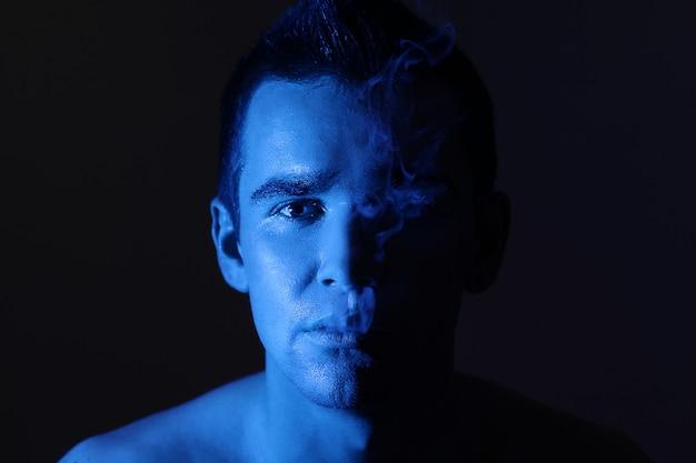 Junges mannporträt, neonblaue farben