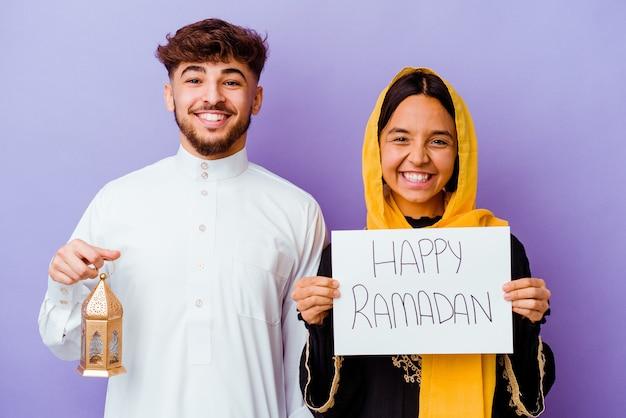 Junges marokkanisches paar, das ein typisches arabisches kostüm trägt, das ramadan lokalisiert auf purpurrotem hintergrund feiert