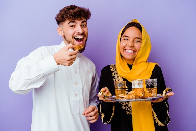 Junges marokkanisches paar, das tee trinkt, der ramadanmonat lokalisiert auf lila hintergrund feiert