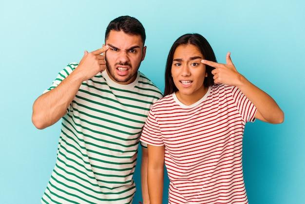 Junges mischrassenpaar isoliert auf blauem hintergrund zeigt eine enttäuschungsgeste mit zeigefinger.