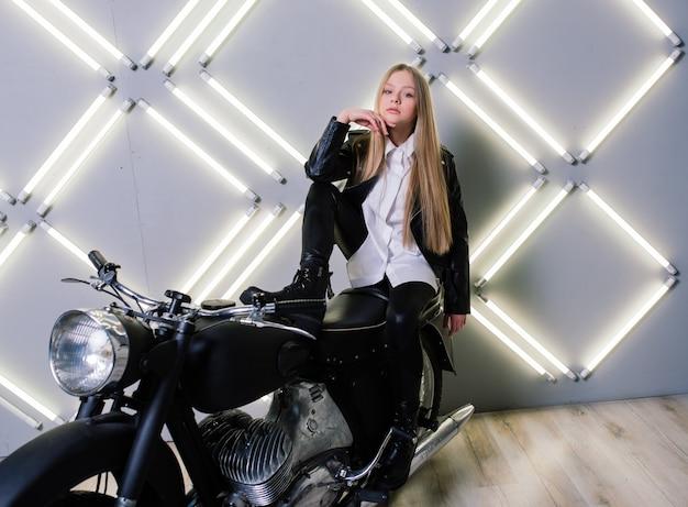 Junges mode-mädchen, das in einem schwarzen leder mit motorrad aufwirft.
