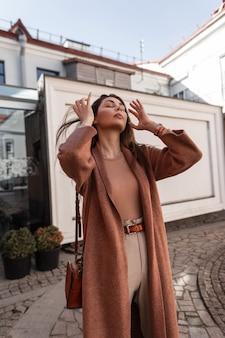 Junges mode-modell junge frau in modischer saisonkleidung glätten das haar, das in der stadt auf der straße steht. europäische hübsche sexy mädchen in elegantem outfit mit lederhandtasche posiert im freien.frühlingslook