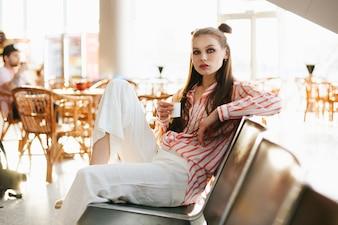 Junges Mode-Modell sitzt mit einem Tasse Kaffee auf den Stühlen im Flughafen