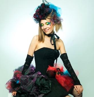 Junges model im karnevalskleid mit kreativem make-up. puppenstil.