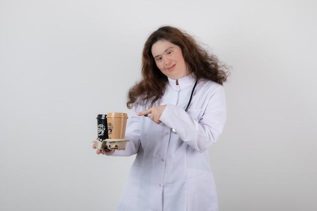 Junges model-mädchen in weißer uniform, das auf einen karton mit tassen kaffee zeigt.