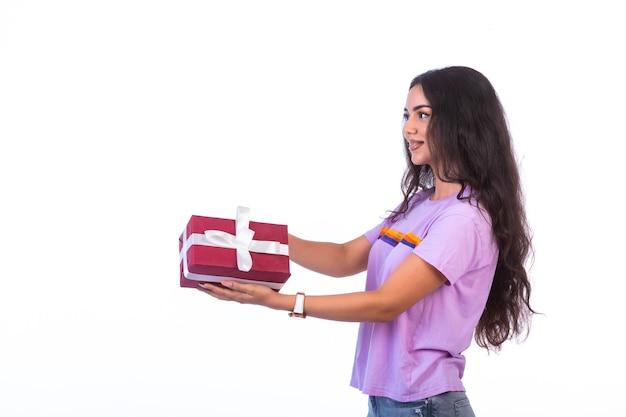 Junges modell, das eine rote geschenkbox, profilansicht hält