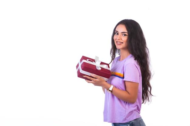 Junges modell, das eine rote geschenkbox, profilansicht hält.