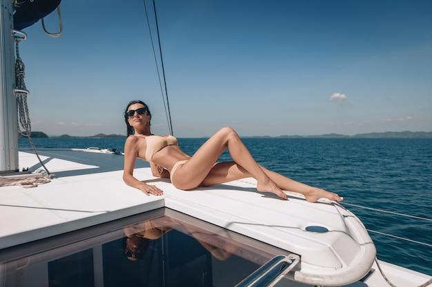 Junges modell, das einen weißen bikini und eine sonnenbrille trägt, die auf einer weißen yacht bräunen