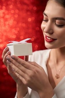 Junges modell, das geschenkpapierbox demonstriert