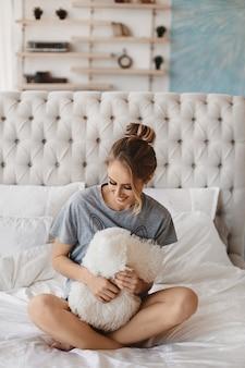 Junges modell frau mit schlankem körper im pyjama posiert morgens auf dem bett hübsches mädchen posiert...