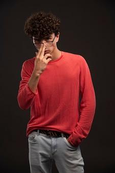Junges modell im roten hemd, das brillen mit den fingern trägt.