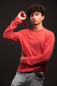 Junges modell im roten hemd, das karate nunchaku hält.