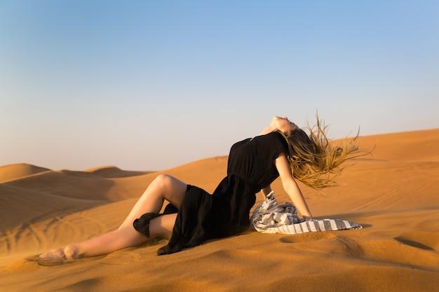 Junges modell im schwarzen kleid, das auf dem sand in der wüste liegend aufwirft