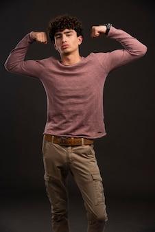 Junges modell in lässigen herbst-winter-outfits, die seine muskeln zeigen.