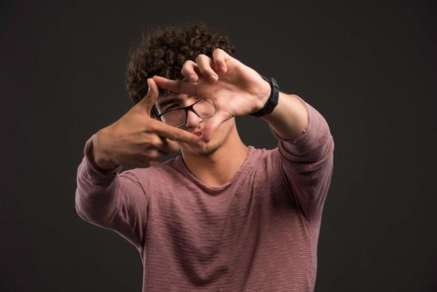 Junges modell mit den lockigen haaren, die rahmenzeichen zeigen.