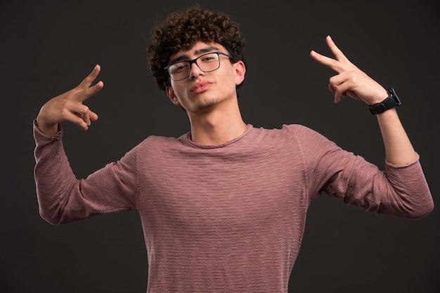 Junges modell mit lockigen haaren, die friedenszeichen zeigen.