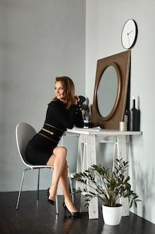 Junges modellmädchen in einem kurzen schwarzen kleid, das am schminktisch im weinleseinnenraum sitzt