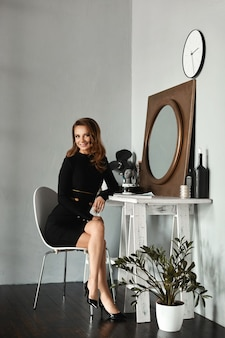 Junges modellmädchen mit schlankem körper in einem kurzen schwarzen kleid, das am schminktisch im weinleseinnenraum sitzt