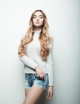 Junges modemodell, das im studio, weißer hintergrund aufwirft