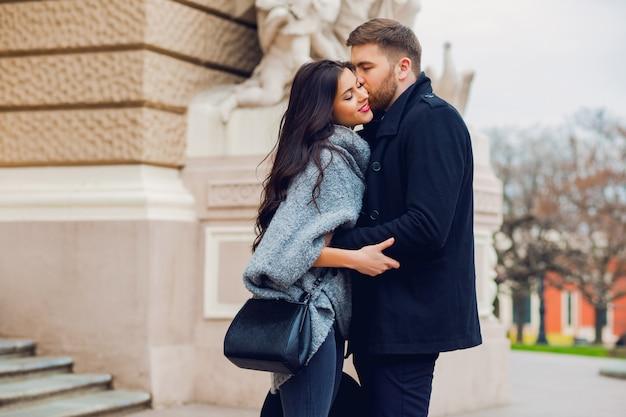 Junges modepaar, das auf der alten straße im sonnigen herbst aufwirft. hübsche schöne frau und ihr hübscher stilvoller freund, der auf der straße umarmt.
