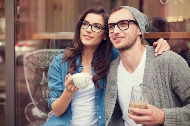 Junges modepaar, das kaffee außerhalb des cafés trinkt