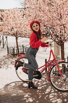 Junges modisches mädchen, das mit rotem fahrrad nahe kirschblüten aufwirft. frau im wollpullover und in den jeans, die gegen sakura lächeln