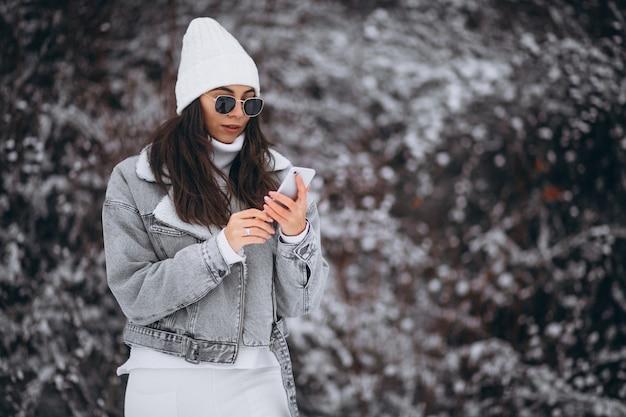 Junges modisches mädchen in einem winterpark unter verwendung des telefons