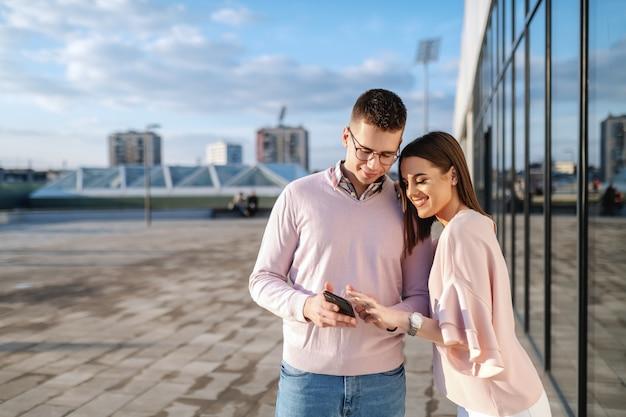 Junges modisches paar, das auf balkon steht und smartphone betrachtet