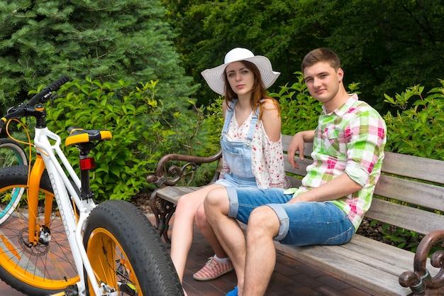 Junges modisches paar, das auf einer bank in der nähe von fahrrädern sitzt, die auf einem gemauerten bürgersteig in einem schönen grünen park geparkt sind?