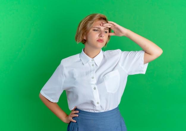 Junges müdes blondes russisches mädchen hält kopf, der seite lokalisiert auf grünem hintergrund mit kopienraum betrachtet