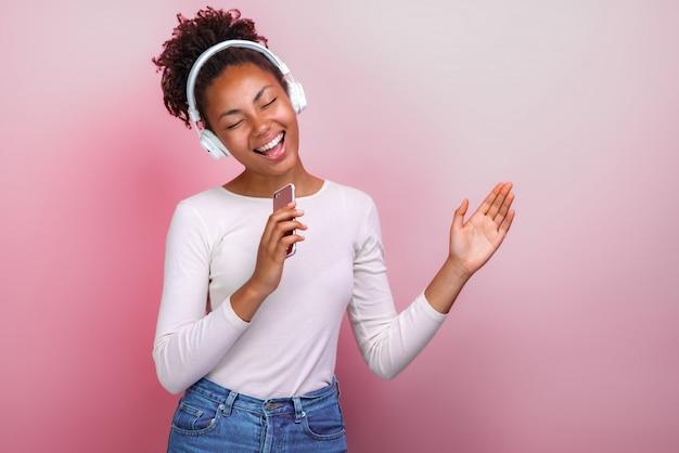 Junges mulattemädchen in den kopfhörern, die den handy singt mit glücklichem gefühl halten