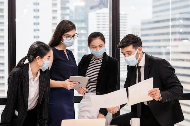 Junges multiethnisches geschäftsteam, das gesichtsmaskenbesprechung trägt und geschäftsplan im büro bespricht
