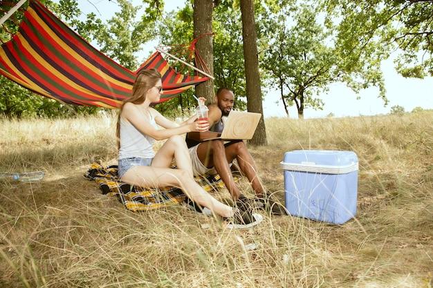 Junges multiethnisches internationales romantisches paar draußen an der wiese im sonnigen sommertag. afroamerikanermann und kaukasische frau, die zusammen picknick haben. konzept der beziehung, sommerzeit.