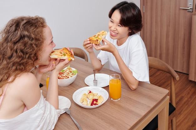 Junges multiethnisches lesbisches paar, das pizza zum abendessen zu hause isst
