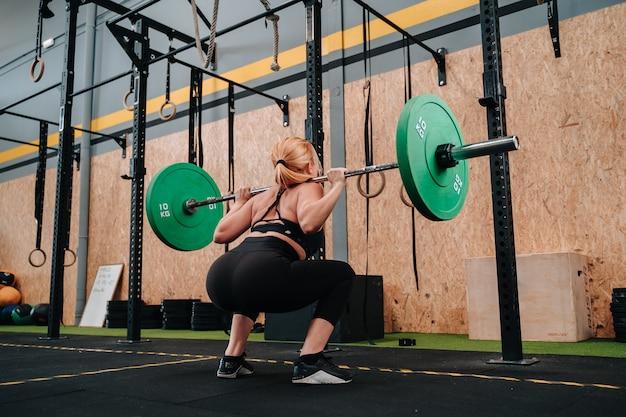 Junges muskulöses mädchen, das eine tote hantel des gewichts in einem crossfit-gymnasium anhebt