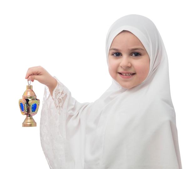Junges muslimisches mädchen im weißen hijab mit laterne