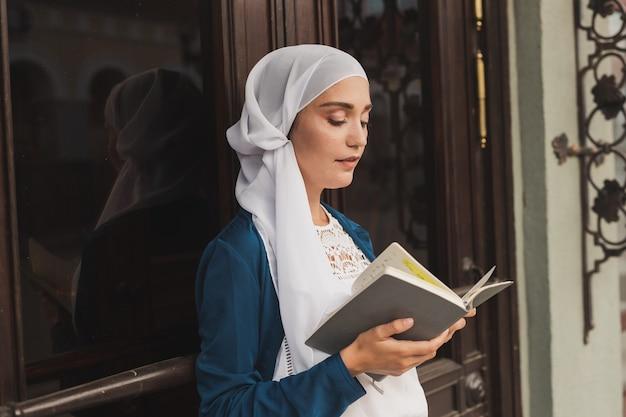 Junges muslimisches mädchen trägt hijab mit islamischem studenten- und wissenskonzept des tagebuchbuchs