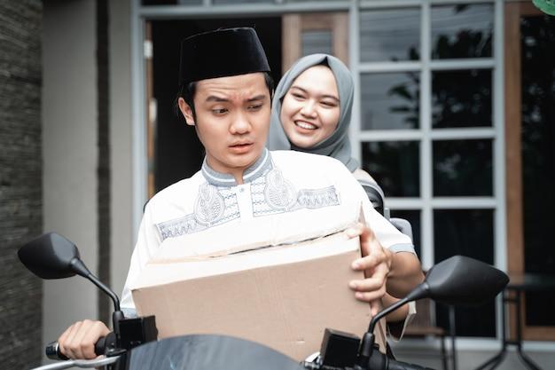 Junges muslimisches paar mit dem motorrad, das nach hause geht und viele waren trägt