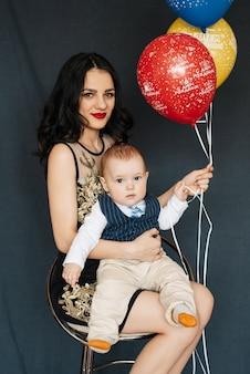 Junges muttermädchen mit jungenbabysohn in ihren armen mit ballonen für geburtstag