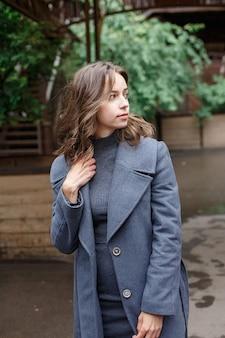 Junges nachdenkliches hübsches mädchen im grauen mantel und im rollkragen wirft draußen auf. streetstyle-porträtfoto-sitzung des attraktiven weiblichen, städtischen fotoshootings des schönen eleganten modells