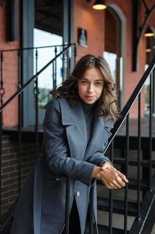 Junges nachdenkliches hübsches mädchen im grauen mantel und im rollkragen wirft vor rotem gebäude auf. streetstyle-porträtfoto-sitzung des attraktiven weiblichen, städtischen fotoshootings des schönen eleganten modells