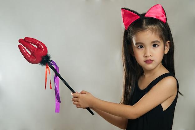 Junges nettes asiatisches mädchenkind, das im schwarzen teufelmode-kostüm ankleidet