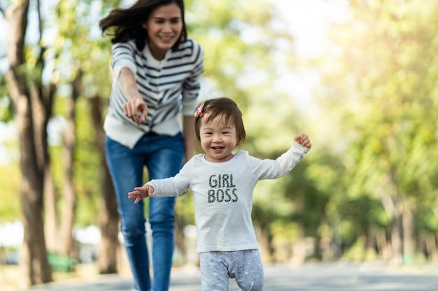 Junges nettes glückliches kleines asiatisches kleinkindmädchen, das in park mit mutter läuft, tochter kümmernd, indem sie sorgfältig kind folgen und halten.