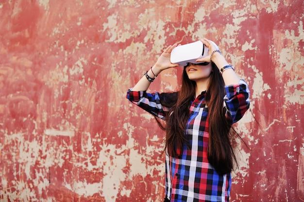Junges nettes mädchen mit dem langen haar im karierten hemd in den gläsern der virtuellen realität auf rotem schmutzwandhintergrund.